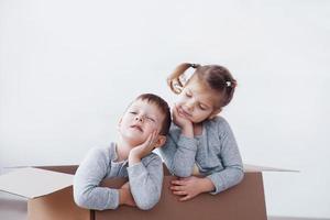 deux un petit garçon et une fille jouant dans des boîtes en carton. photo conceptuelle. les enfants s'amusent
