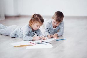 les enfants sont allongés par terre en pyjama et dessinent avec des crayons. peinture d'enfant mignon par des crayons photo