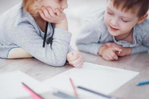 les enfants sont allongés par terre en pyjama et dessinent avec des crayons. enfant mignon peinture par crayons.main d'enfant fille et garçon dessiner et peindre avec un crayon. vue rapprochée photo