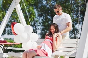 bébé en attente. femme enceinte avec son mari bien-aimé s'asseoir sur un banc. la main du mari embrasse une femme au ventre rond. parentalité. femme enceinte vêtue d'une robe blanche en cerise avec un noeud rouge. fermer. neuf mois photo