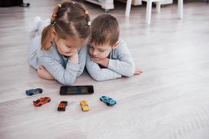 enfants utilisant des gadgets numériques à la maison. frère et soeur en pyjama regardent des dessins animés et jouent à des jeux sur leur tablette technologique photo