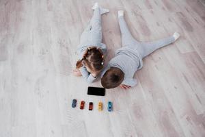 vue de dessus. enfants utilisant des gadgets numériques à la maison. frère et soeur en pyjama regardent des dessins animés et jouent à des jeux sur leur tablette technologique photo