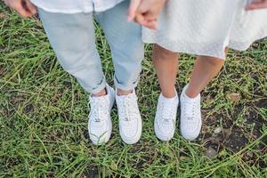 couple debout sur terrain en herbe. pieds et chaussures de jeune couple. photo