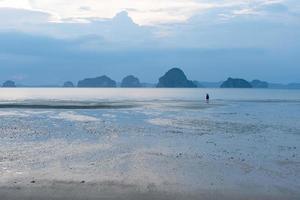 paysage de bel océan et plage au coucher du soleil avec un couple marchant en arrière-plan photo
