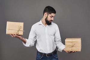 beau mec romantique regarde la boîte et fait un choix. tenant une grande boîte-cadeau pour son couple, sur fond gris. photo