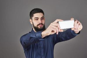 Jeune homme d'affaires hipster barbu parlant de photo de selfie avec un téléphone intelligent souriant et regardant le téléphone sur fond gris studio