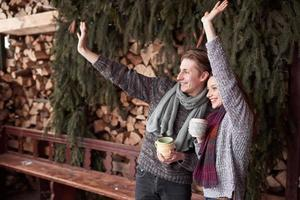 photo d'un homme heureux et d'une jolie femme avec des tasses en plein air en hiver. vacances d'hiver et vacances. couple de noël heureux homme et femme boivent du café chaud. bonjour voisins