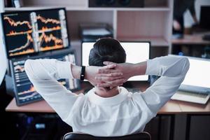 développer de nouvelles approches. vue arrière du jeune homme en tenue décontractée tenant la main à l'arrière de la tête et travaillant assis au bureau dans un bureau créatif photo