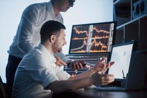 une équipe de courtiers en bourse a une conversation dans un bureau sombre avec des écrans d'affichage. analyser des données, des graphiques et des rapports à des fins d'investissement. commerçants créatifs de travail d'équipe photo