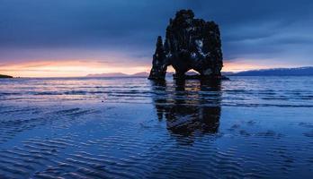 est un rocher spectaculaire dans la mer sur la côte nord de l'Islande. les légendes disent que c'est un troll pétrifié. sur cette photo hvitserkur se reflète dans l'eau de mer après le coucher du soleil de minuit