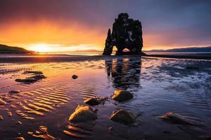 hvitserkur est un rocher spectaculaire dans la mer sur la côte nord de l'Islande. les légendes disent que c'est un troll pétrifié. sur cette photo hvitserkur se reflète dans l'eau de mer après le coucher du soleil de minuit