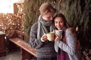 photo d'un homme heureux et d'une jolie femme avec des tasses en plein air en hiver. vacances d'hiver et vacances. couple de noël d'homme et de femme heureux boivent du vin chaud. couple amoureux