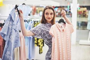 concept de vente, de mode, de consommation et de personnes - jeune femme heureuse avec des sacs à provisions choisissant des vêtements dans un centre commercial ou un magasin de vêtements photo