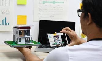 un concepteur de maison utilise un smartphone pour appeler une maison modèle par vidéo afin de parler aux clients. photo