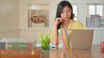 une jeune femme utilise un ordinateur portable pour travailler, elle travaille à domicile et est fatiguée. photo