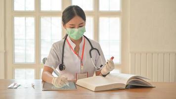 les infirmières portent des gants et un masque utilisent une tablette pour enregistrer les résultats des tests sanguins pour les personnes infectées par le virus covid-19. photo