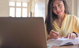 Une étudiante asiatique cherche des informations à partir d'un ordinateur portable et prend des notes. elle se prépare à l'examen d'entrée à l'université. photo