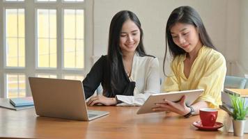 deux femmes asiatiques avec ordinateur portable et tablette travaillant à la maison. pour empêcher la propagation du coronavirus. photo