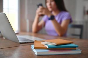 un ordinateur portable avec un ordinateur portable sur la table et une jeune femme utilisant un smartphone à l'arrière. photo