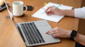 la main d'une jeune femme utilisant un ordinateur portable et rédigeant un rapport, elle travaille à domicile. photo