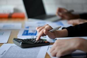 fille d'affaires travaillant avec une calculatrice sur le bureau au bureau. photo