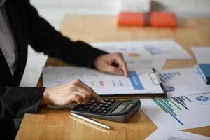 photo recadrée du personnel comptable utilisant des calculatrices et des graphiques pour payer les impôts annuels.
