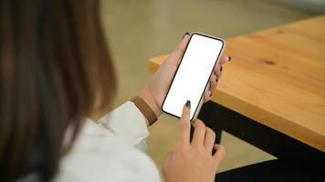 gros plan d'une jeune femme tient et utilise le smartphone à écran blanc. photo