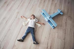 l'enfant fait semblant d'être pilote. enfant s'amusant à la maison. vacances d'été et concept de voyage. vue de dessus photo