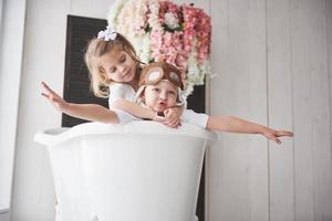 portrait d'une fille et d'un garçon au chapeau de pilote jouant dans la salle de bain chez les pilotes ou les marins. le concept de voyage, d'enfance et de réalisation de rêves photo