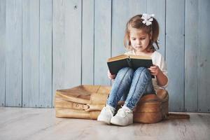 prêt à grand voyage. heureuse petite fille lisant un livre intéressant portant une grosse mallette et souriante. concept de voyage, de liberté et d'imagination photo