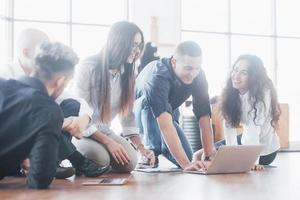 jeunes créatifs dans un bureau moderne. un groupe de jeunes gens d'affaires travaille avec un ordinateur portable. pigistes assis par terre. réalisation d'entreprise de coopération. concept de travail d'équipe photo