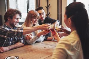 groupe de jeunes amis s'amusant et riant en dînant à table au restaurant photo