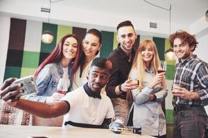amis s'amusant au restaurant.deux garçons et quatre filles buvant en faisant un selfie, faisant un signe de paix et riant. au premier plan femme tenant un téléphone intelligent. tous portent des vêtements décontractés photo