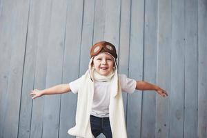 bel enfant souriant en casque sur fond bleu jouant avec un avion. concept pilote vintage photo
