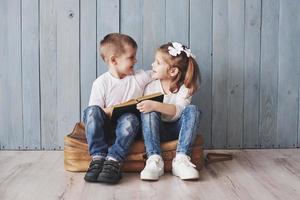prêt à grand voyage. heureuse petite fille et garçon lisant un livre intéressant portant une grande mallette et souriant. concept de voyage, de liberté et d'imagination photo