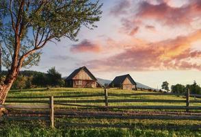 beau paysage de montagne d'été au soleil. vue sur la prairie clôturée clôture. paysage rural photo