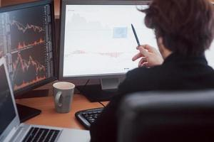 développer de nouvelles approches. vue arrière du jeune homme en tenue décontractée travaillant assis au bureau dans un bureau créatif photo