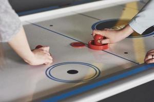 mains de jeunes tenant un attaquant sur une table de hockey sur air dans la salle de jeux photo
