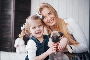 famille aimante heureuse. mère et sa fille enfant fille jouant et étreignant adorable carlin photo