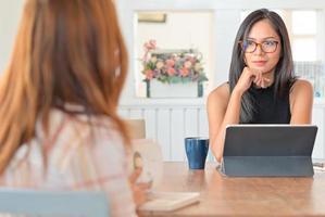 deux jeunes femmes discutant avec une tablette dans le salon. ils sont assis espacés pour empêcher le virus. photo
