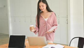 une étudiante tenant une tasse de café et un document à la main avec un ordinateur portable sur la table. photo