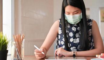 photo recadrée de jeunes femmes et d'une tablette travaillant à la maison. elle est protégée de l'épidémie de coronavirus.