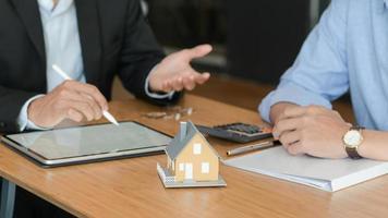 les clients écoutent les promotions des courtiers à domicile. avec maisons modèles et tablette sur la table. photo