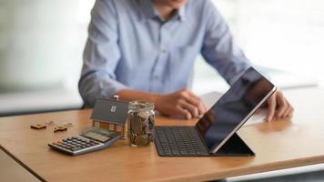 ordinateur portable, pièce de monnaie dans une bouteille en verre, calculatrice avec une maison modèle sur la table et un arrière-plan flou des gens assis en train de regarder des documents. photo