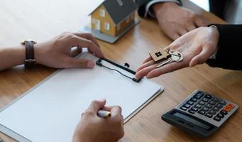 signer un contrat d'achat de maison entre l'acheteur et le vendeur et remettre la clé de la maison. photo