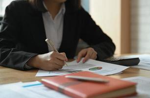 les femmes d'affaires travaillent sur la table du bureau. elle pointa le graphique à analyser. photo