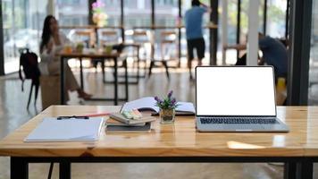 photo recadrée d'un ordinateur portable, de notes et de fournitures de bureau sur un bureau en bois dans un espace de travail partagé confortable.