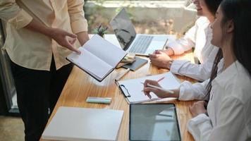 un groupe de jeunes professionnels recherche et fabrique des informations pour préparer de futurs projets. avec un ordinateur portable et un bloc-notes. photo
