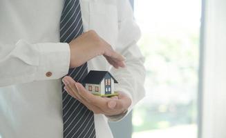 l'agent d'assurance tient en main un modèle de maison montrant le symbole de l'assurance habitation. photo