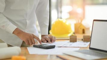 les architectes utilisent des calculatrices pour concevoir des plans de maison pour de nouveaux projets. photo